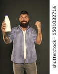 Small photo of Dairy foods are good sources of protein and calcium. Bearded man holding bottle of dairy drink on grey background. Happy hipster enjoying dairy diet. Dairy menu.