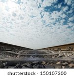 railway to horizon under cloudy sky - stock photo
