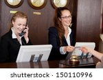 Stock photo two beautiful young stylish receptionists at a reception desk one talking on the telephone and the 150110996