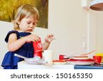 serious toddler girl is playing ... | Shutterstock . vector #150165350