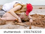 Young woman with blonde hair and red cap digs for crystals in Oklahoma