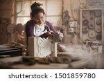 Female Sculptor Cutting A White ...