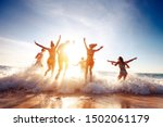 Small photo of Big group of seven happy friends is having fun and runs at sunset beach to sun light and waves
