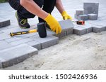 Small photo of The master in yellow gloves lays paving stones in layers. Garden brick pathway paving by professional paver worker. Laying gray concrete paving slabs in house courtyard on sand foundation base.
