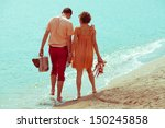 Happy honeymoon (vacation) concept. Young happy married couple of hipsters walking on beach holding each other and holding their shoes, vintage suitcase and photocamera. Sunny summer day. Outdoor shot - stock photo