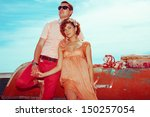 Happy honeymoon (vacation) concept. Young married couple of hipsters in trendy clothes holding hands and posing over old boats background. Sunny summer day. Vintage style. Copy-space. Outdoor shot - stock photo
