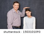 Small photo of Studio half-length shot of happy tall man showing with hand at height of upset short girl standing beside him and looking with perplexity at camera, over gray background. Variety of person's heights