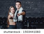 Small photo of Young sporty couple guy and girl standing in gym. During this, the white scumbag is held on the neck. Standing on a black background and looking at the camera.