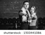 Small photo of Young sporty couple guy and girl standing in gym. During this, the white scumbag is held on the neck. Standing on a black background and looking at each other. Black and white.