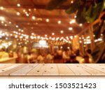 Stock photo empty wooden table top with blur coffee shop or restaurant interior background 1503521423
