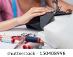 Young tailor sews a pair of...