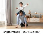 Small photo of Happy funny family excited little boy playing with father at home, young dad crawling on floor carrying cute small child son on back giving kid piggyback ride having fun spending time together