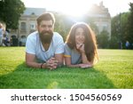 Adding some romance. Holiday romance of bearded man and sexy woman. Couple in love relaxing on green grass on sunny summer outdoor. Feeling romance. Love and romance.