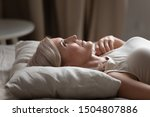Small photo of Sleepless mature woman with open eyes lying on soft pillow close up, suffering from insomnia, lack of sleep, older female lying in bed in the morning, looking up, thinking, early awakening