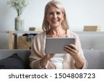 Small photo of Head shot portrait close up happy mature woman using computer tablet, looking at camera, laughing at funny joke or video in social network, older female holding electronic device, sitting on couch