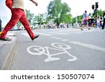 Man in red trousers crossing street with traffic - stock photo