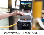 Small photo of Japan, Tokyo - Sep 01 2019: Closeup of a eldery woman's hand waive a prepaid card on the contactless reader machine in a city bus. Public transportation, Japan's population ages, Senior discounts.