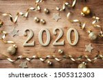 Small photo of Happy New Year festive background with golden numbers 2020 and Christmas decorations on vintage wooden table top view.