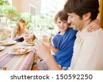 family of four gathering around ... | Shutterstock . vector #150592250