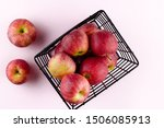 Red apples in the metallic black basket on the light pink background. Top view flat lay composition. Space for text template. Fresh autumn fruit wallpaper. - stock photo