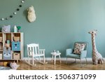 Small photo of Scandinavian interior design of playroom with wooden cabinet, armchairs, a lot of plush and wooden toys. Stylish and cute childroom decor. Eucalyptus background walls. Copy space. Template.