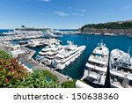 MONTE CARLO, MONACO - JUN 21: View on Port Hercules with luxurious yachts and a cruise ship on June 21, 2010 in Monte Carlo, Monaco. It is the only deep-water port in Monaco. The port has been in use since ancient times. - stock photo