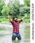 Satisfied fisher. Fisher masculine hobby. Fishing requires you to be mindful and fully present in moment. Fisher fishing equipment. Fish on hook. Brutal man wear rubber boots stand in river water.