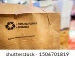 Small photo of Brown paper bag that is 100% recyclable and reusable on a counter. A printed plea for user to recycle and reuse this bag as a form of packaging.