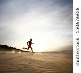 Stock photo man running on beach at sunset 150676628
