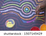 Small photo of DERBY, WA - SEP 10 2019:Aboriginal artist dot painting.Before Indigenous Australian art was ever put onto canvas the Aboriginal people would smooth over the soil to draw sacred ceremony designs.