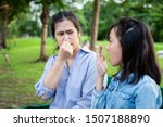 Small photo of Asian daughter child girl checking breath with her hand,teen girl horrible bad breath,foul mouth,mother closing her nose,very bad smell,feeling stinks,facial expression,health care,halitosis concept