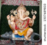 Small photo of statue of lord ganesh wearing gold jewellery, crown, holding modak, trident, trisul in his hands sitting on mouse rat isolated on colorful rose and green grass background. indian ganpati festival.