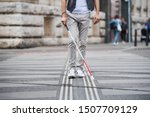 Small photo of Midsection of young blind man with white cane walking across the street in city.