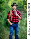 Small photo of Cowboy ranch worker. Bourbon whiskey. Western culture. Man wearing hat hold rope and flask. Lasso tool American cowboy. Brutal cowboy drinking alcohol. Man handsome cowboy nature background.