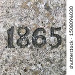 The year 1865 carved in stone and painted in black – a detail of an inscription produced that year. Covered by lichen in different colours