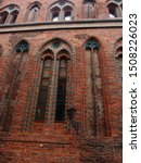 Gothic windows of a Old Town Hall (Szczecin Poland), red brown bricks. window decorations, arches, medieval architecture, antique street lamp, a row of arch windows, historical district of Szczecin
