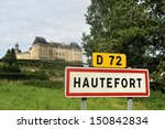 Town sign of the city of Hautefort in France. At the background the castle of Hautefort. - stock photo