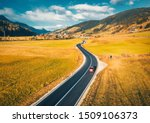 Small photo of Aerial view of the road in mountain valley at sunset in autumn. Top view of asphalt roadway, car, hills with orange grass, blue sky, trees, buildings. Highway and fields in fall. Colorful landscape