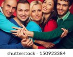 Happy people concept. Portrait of five stylish close friends hugging, smiling and posing over red background. Guys having fun. Hipster style. Studio shot - stock photo