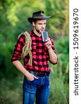 Small photo of Cowboy ranch worker. Brutal cowboy drinking alcohol. Man handsome cowboy nature background. Bourbon whiskey. Western culture. Man wearing hat hold rope and flask. Lasso tool American cowboy.
