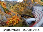 Autumn scenery of colorful foliage on the rocky cliffs & water release from Hoheikyo Dam, a reservoir in a gorge under environmental protection in Shikotsu-Toya National Park, Sapporo, Hokkaido, Japan