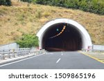 Small photo of Road tunnel in mountains. Mountain road tunnel with luminous safety lights and yellow road line. Tunnel on the highway. Automobile trip. Pathway with tunnel. Drive through the mountain
