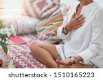 Small photo of Self-Healing Heart Chakra Meditation. Woman sitting in a lotus position with right hand on heart chakra and left palm open in a receiving gesture. Self-Care Practice at Home