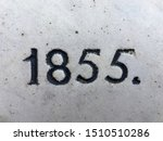 The year 1855 carved in stone and painted in black. Sparsely covered with lichen