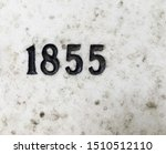The year 1855 carved in stone and painted in black. Covered with lichen