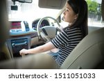 Small photo of Young asian woman driveing car checking on mirror check behind going reverse keeps wheel turning around. Japanese girl new driver parking car. ride car backward exam vehicle concept.
