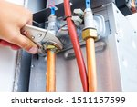 Plumber repairing a gas boiler of a heating home system in the boiler room. Close-up, selective focus. - stock photo