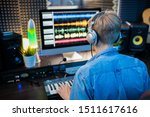 Rear view of young man in headphones looking at computer screen while making music and recording it in modern studio - stock photo