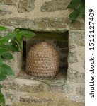 Small photo of Woven Straw Bee Skep on a Ledge Built into a Wall by an Orchard in the Village of Godolphin in Rural Cornwall, England, UK