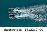 Aerial drone top down photo of 2 men competing in jet ski watercraft in high speed in deep blue open ocean sea
